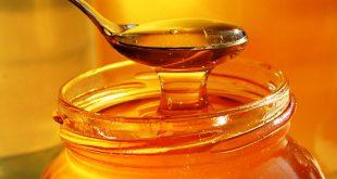 Miele raccolto con un cucchiaino da un barattolo